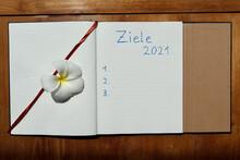 Die Festlegung Von Zielen Für Das Jahr 2021 Auf Einem Linierten Papier Auf Einer Holzunterlage Mit Und Ohne Eine Blüte.