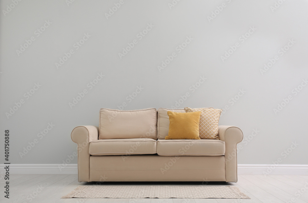 Fototapeta Comfortable beige sofa near light wall indoors, space for text. Simple interior