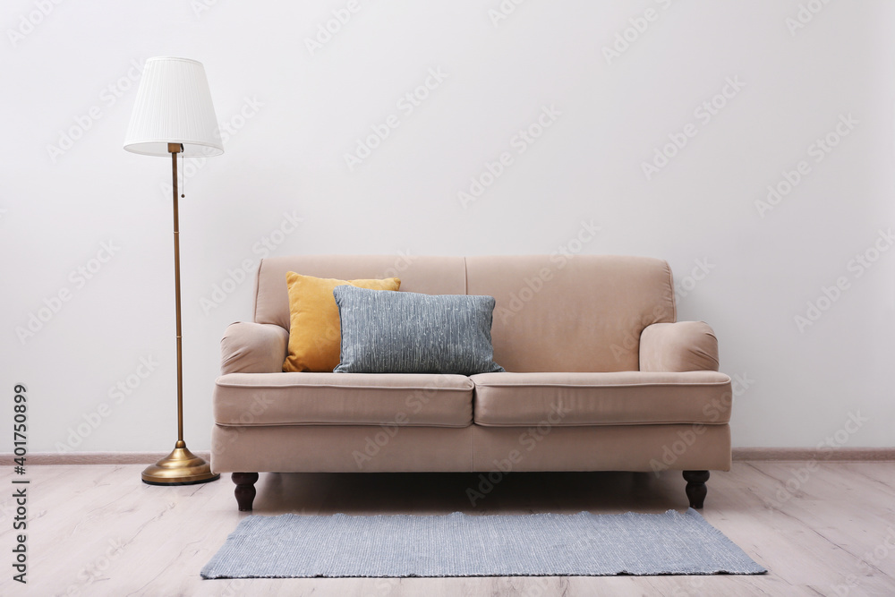 Fototapeta Simple room interior with comfortable beige sofa