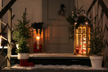 Decorative Lanterns And Small Christmas Trees Near House Entrance