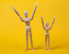 Happy Wooden Puppets With Hands Raised Up On Yellow Background. Positive Emotions