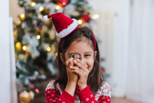 A Happy Little Hispanic Girl In A Christmas Sweater And A Funny Head Hoop Holding A Glass Snowball