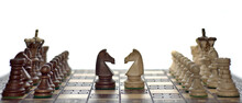 Chess Faceoff Of Both Knight Horses On Top Of A Chess Board In Front Of A White Background Surrounded By The King, Queen, Bishop, Rook And Pawns