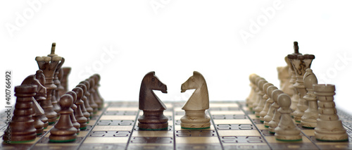 Carta da parati Chess faceoff of both knight horses on top of a chess board in front of a white