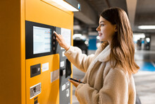 Elegant Young Girl Pays For Ticket In Parking Meter. Woman Near Terminal In The Underground Parking