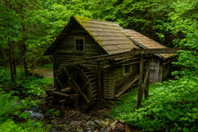Old Wooden House With A Water Wheel In The Green Forest