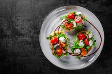 Italian Bruschetta With Roasted Tomatoes, Mozzarella Cheese, Balsamic Vinegar And Herbs On Plate