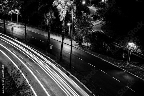 Fototapeta A grayscale shot of an empty road during the night obraz na płótnie