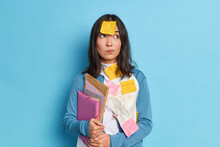 Thoughtful Asain Woman Has Sticky Notes On Clothes And Forehead Stads Pensive Works Hard During Deadline Holds Folders With Documents Isolated Over Blue Background. Busy Female Employee In Office