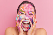 Headshot Of Overjoyed Happy Ethnic Woman Keeps Hands On Cheeks Giggles Positively Keeps Mouth Opened Has Creative Makeup Smeared Face With Watercolor Paints Stands Naked Against Rosy Background