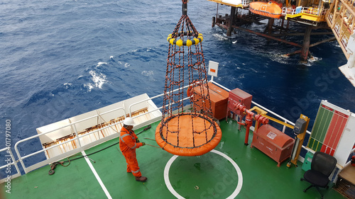 Fotografering Workers are lifted by the crane to the offshore platform, Transfer crews by personal basket from the platform to crews boat