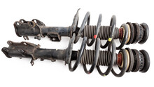 Two Shock Absorber Struts With Black Springs After Being Used On A Car During Replacement And Repair On A White Isolated Background. Used Spare Parts. Auto Parts Catalog.