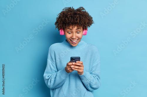 Billede på lærred Photo of African American teenage girl stares impressed at smartphone display re
