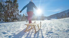 LOW ANGLE: Unrecognizable Young Woman Runs Along A Snowy Meadow Pulling Her Sled