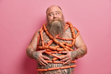 Food Addiction And Bad Nutrition Concept. Plump Bearded Man Stands Wrapped In Sausages Has Big Fat Abdomen Tattooed Body And Thick Beard Leads Unhealty Lifestyle Poses Against Pink Background