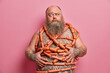 Leinwandbild Motiv Puzzled bearded man wrapped with sausages has fat tattooed belly excess weight isolated over pink background. Obese adult male human eats junk food. Harmful nutrition and unhealthy lifestyle