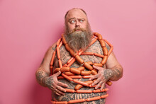 Puzzled Bearded Man Wrapped With Sausages Has Fat Tattooed Belly Excess Weight Isolated Over Pink Background. Obese Adult Male Human Eats Junk Food. Harmful Nutrition And Unhealthy Lifestyle