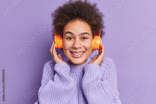 Fényképezés Pretty African American teenager feels amused smiles broadly shows teeth keeps h