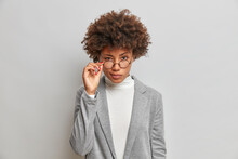Beautiful African American Woman Looks Attentively Through Round Glasses Dressed In Formal Clothes Analyses Necessary Information Poses Against Grey Background. Let Me Think How To Do Better