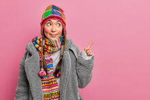Shocked Eastern Girl With Two Pigtails Points Aside On Free Space Wears Hat And Winter Coat Demonstrates Advertising Content Isolated Over Pink Background. I Recommend To Use This Blank Place