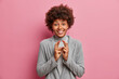 Leinwandbild Motiv Cheerful dark skinned woman makes wish and hopes for good luck crosses fingers smiles toothily hopes dreams come true dressed in formal grey clothes isolated over pink background. Body language