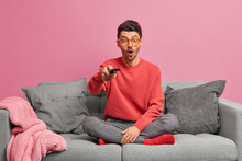 Weekend Entertainments And Pastime Concept. Shocked Adult European Man Watches Interesting Movie Indoors Stares Surprised Fascinated By Scene Holds Remote Controller Sits Crossed Legs On Sofa