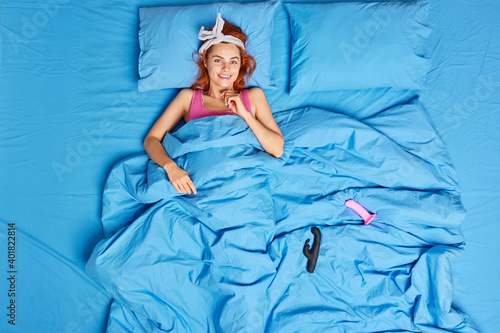 Canvas Print Overhead shot of smiling ginger young woman lying under blanket being single satisfies herself with sex toys before sleep wears headband dressed in pajama