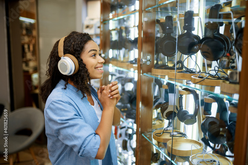 Foto Woman trying on headphones in speaker system store