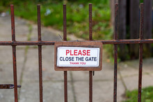 A Please Close The Gate Sign Hanging On A Rusty Metal Gate