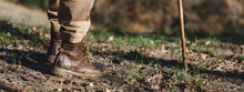 Horizontal Banner Close-up Dirty Boots Of Hiker Man Walking In A Muddy Path. Unrecognizable Person In Outdoors Activities.