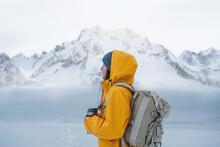 Alone Brave Woman Traveler With Backpack Looking Away To Winter Mountains. Female Explorer Wearing Rucksack Among Winter Landscape Travel At Holidays Journey