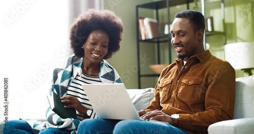 Obraz Family couple together resting at home. Pretty African American woman sitting on sofa and reading enjoying favorite book while her husband typing and browsing on laptop. Marriage concept - fototapety do salonu