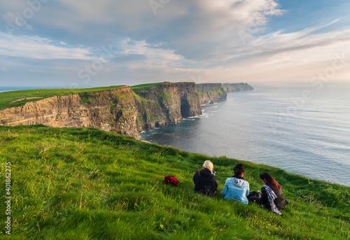 Fotografie, Obraz Girls sitting near the edge of the cliffs of Moher
