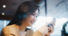 Beautiful Young Adult Asian Woman Using Smartphone In Coffee Shop, Happy Smiling. People Modern Lifestyle, Internet Communication Technology, Or Online Shopping Concept. Captured On RED Komodo 6K