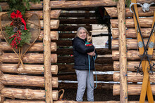Older Mature Woman Holds A Yorkshire Terrier Dog While Standing In A Decorated Log Cabin Hut