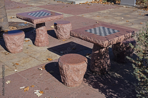 Chessboards or checkerboards inlaid into stone tables in a public park in southern California provide year round outdoor recreation for players Fototapet