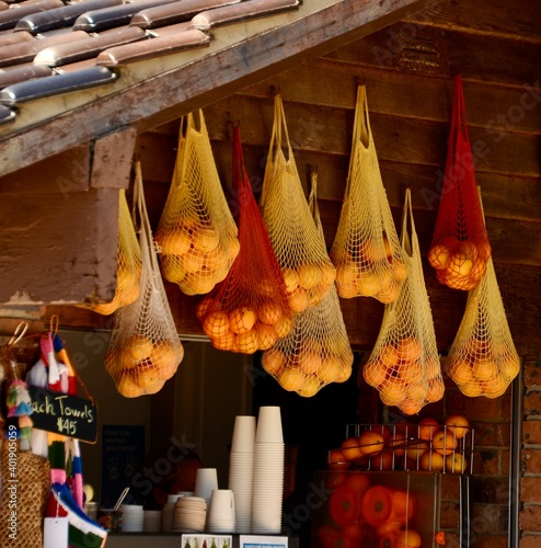 Fotografering String bags containing oranges hanging from the ceiling of a beachside cafe at C