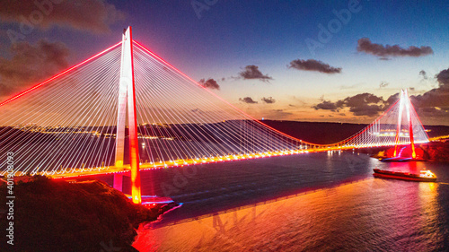 Fotografie, Obraz The miraculous view of Yavuz Sultan Selim Bridge, taken at sunset, illuminating the city with its lights