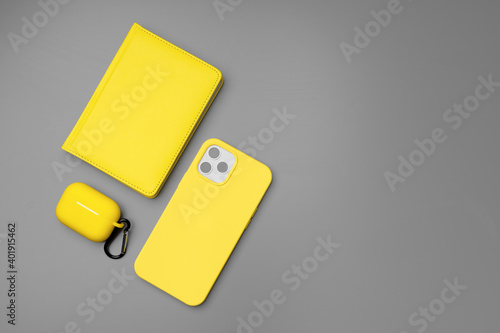 Yellow notepad, smartphone and earphones on gray background