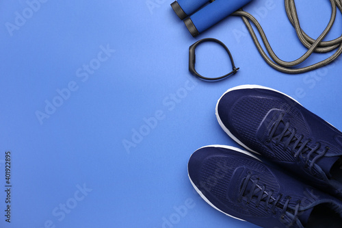 Fototapeta Sportive shoes and jumping rope on color background obraz