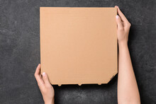 Hands With Cardboard Pizza Box On Dark Background