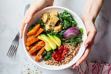Woman Hands Eating Vegan Salad Of Baked Vegetables, Avocado, Tofu And Buckwheat Buddha Bowl, Top View. Plant Based Food Concept.