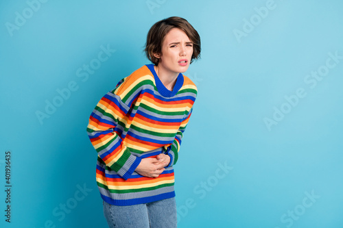 Obraz Portrait of depressed frustrated girl touching belly feeling bad healthcare spasm period isolated over bright blue color background - fototapety do salonu