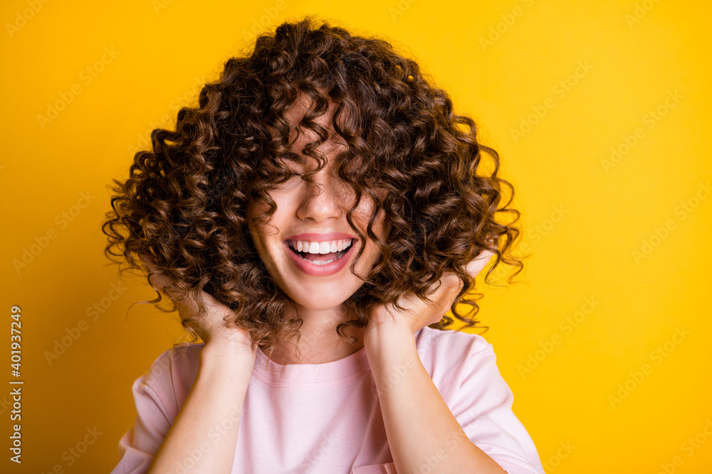 Fototapeta Photo portrait of girl with curly hairstyle wearing t-shirt laughing touching hair isolated on bright yellow color background
