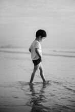 A Black And White Photo Of A Boy Walking On The Beach. He Was Looking Down At His Wet Feet On The Shallow Water Of The Beach.