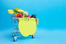 Metal Shopping Cart With Fruits And Vegetables On A Blue Background. Toy Miniature Shopping Trolley