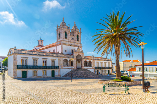Canvas-taulu Sanctuary of Our Lady of Nazare catholic church in cobblestone square with palm