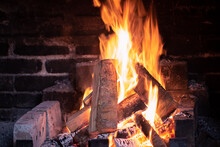 Wooden Logs Burning In A Flame In A Fireplace.