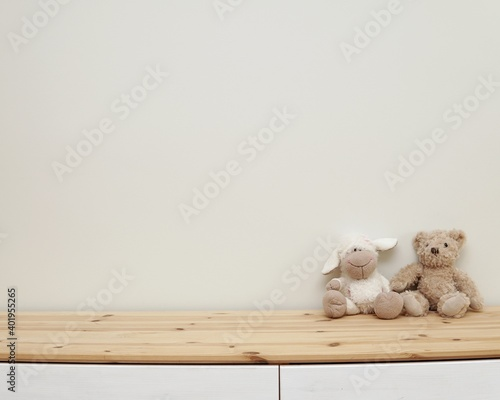 Empty nursery wall mockup, wooden shelf, soft toys, space for baby room wall decal, stickers, framed print or poster presentation.