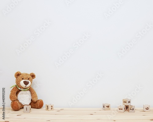 Empty nursery wall mockup, soft toy and wooden cubes, space for baby room wall decal, stickers or framed art presentation.